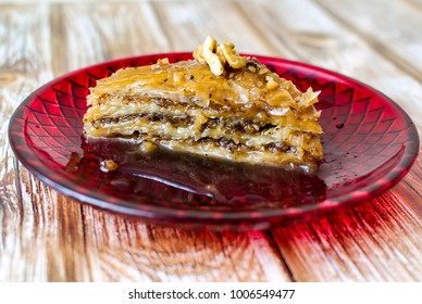 Sweet pastry - Baklava in a red dish on an old wooden table