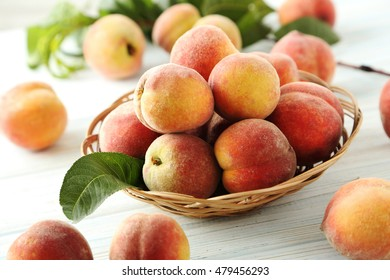 Sweet peach fruit in basket on white wooden table