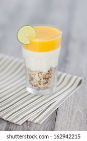 Sweet peach mousse with organic yoghurt served in panna cotta way. Fresh fruit and grain dessert decorated with lime slice.
