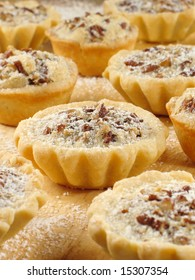 Sweet pecan tarts with a light sprinkle of confectioner's sugar.