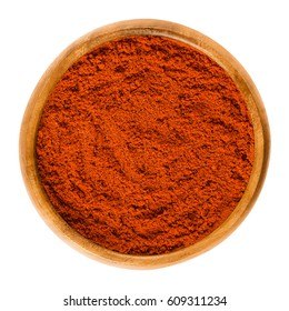 Sweet pepper red paprika powder in wooden bowl. Ground spice made from air-dried and smoked bell peppers, Capsicum annuum. Hungarian cuisine. Macro food photo close up from above on white background.