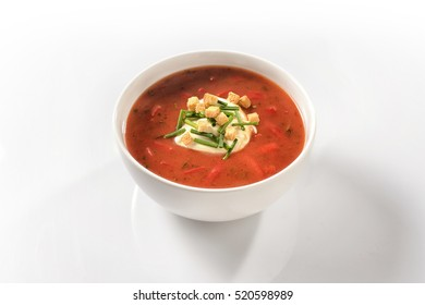 Sweet pepper soup with peppers and sour cream in a white porcelain cup