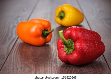 sweet peppers on the brown wooden table