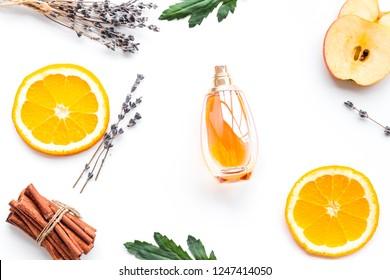Sweet perfume with fruit fragrance. Bottle  of perfume near apple, orange, lavender, cinnamon on white background top view
