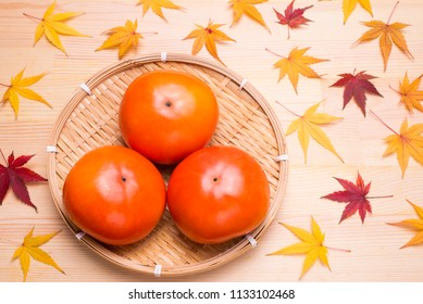 Sweet persimmon fruit on a bampoo sieve with autumn leaves on wooden table