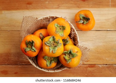 Sweet persimmon in  wooden basket on wooden background,top view