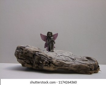 Sweet Pewter Angel Perched sitting on an old piece of drift wood