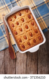 Sweet pie Basbousa (Namoora) with almond in baking dish on the table. vertical top view