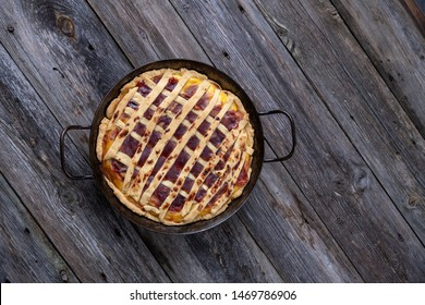 sweet pie in iron pan on wooden ground