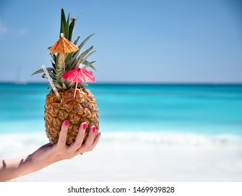 Sweet pineapple cocktail in female hand with caribbean beach background. Travel destination. Summer vacation