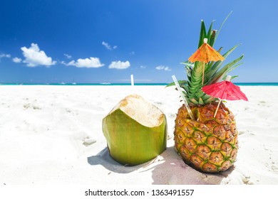 Sweet pineapple and coconut cocktail on sand with caribbean beach background. Travel summer vacation banner with copy space for your text