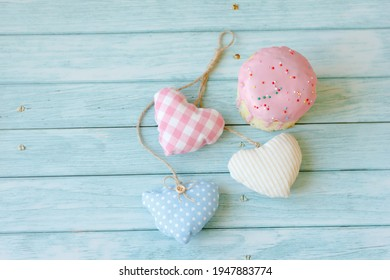 Sweet pink cake dessert and three colored hearts on blue wooden background. View on top, copy space