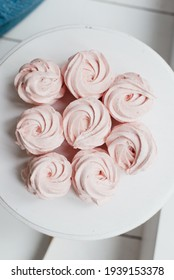 sweet pink meringue on a white plate on the table sweet food