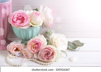 Sweet pink roses flowers in vase  in ray of light on white painted wooden background.  Selective focus. Place for text.
