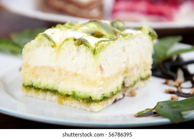 Sweet pistachio dessert with vanilla cream and nuts and chocolate on white plate with juice.