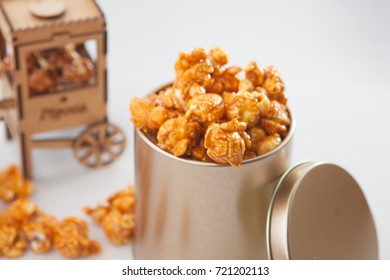 Sweet pop corns on metal bucket with small pop corn cart behind
