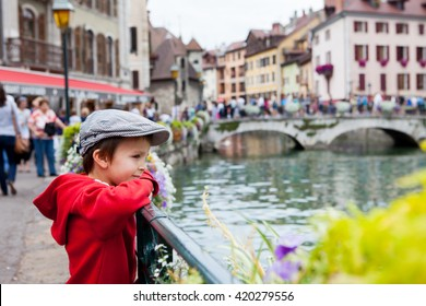 Sweet portrait of preschool boy in the town of Annecy, France, springtime, enjoying the view of the channel