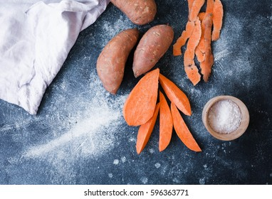 Sweet potato. Cut sweet potato over blue table. Sweet potato sliced ready to prepare baked pie with vegetables. Top view.
