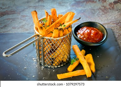 Sweet potato fires in metal chip basket, with ketchup.
