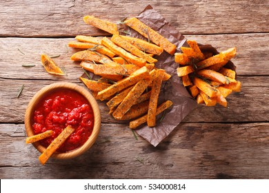 sweet potato fries with herbs and ketchup closeup on the table. Horizontal view from above