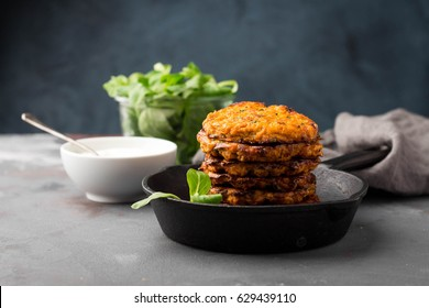 Sweet potato fritters in skillet served with fresh green salad and yogurt sauce