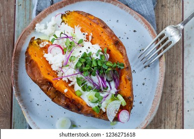 Sweet potato with mashed avocado, yogurt, feta cheese and sprouts