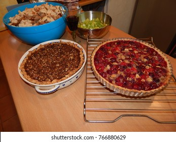 Sweet potato pie and cranberry and pecan pie - with glass of red wine, blue bowl of stuffing ingredient and metal bowl of chopped celery in background.