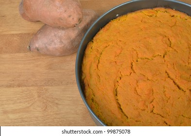 Sweet Potato Pie with Sweet Potatoes in the Background on a Wooden Table with Room for your Text