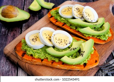 Sweet potato toasts with avocado, eggs and chia seeds on a wood board. Table scene with a wooden background.
