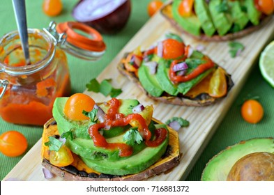 Sweet potato toasts with guacamole and spicy salsa on wooden board