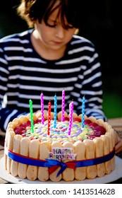 Sweet preteen boy, celebrating his birhtday with colorful cake outdoors, sitting on bench