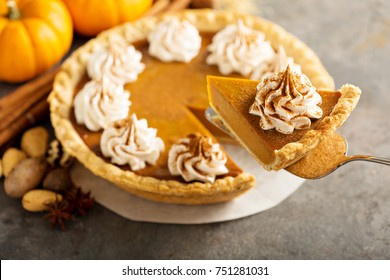 Sweet pumpkin pie decorated with whipped cream and cinnamon with a slice taken out