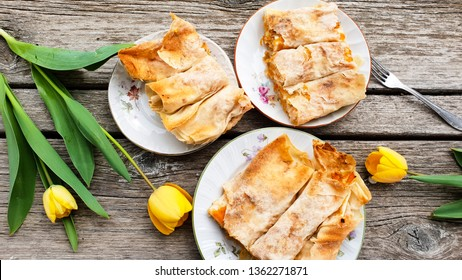 Sweet pumpking home made  pie  with filo pastry  and  yellow tulips on wooden background