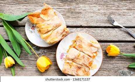 Sweet pumpking home made  pie  with filo pastry and cream filling  and  yellow tulips on wooden background