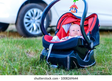 Sweet quiet little baby resting outdoors in a carrycot placed on the grass in the shade of a car watching the camera with a calm expression