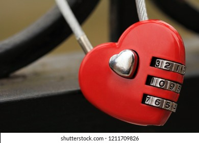 Sweet red heart lock on iron black bridge with pattern. Combination padlock locked. Valentines day background. Romance concept. Love store