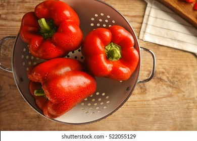 Sweet red peppers in colander on wooden background