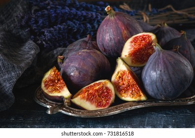 Sweet red ripe figs on a bunch of lies on a beautiful metal stand .