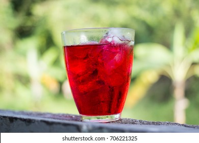 sweet red water in glass, red water juice, Red nectar quenches thirst, Water is a mixture of red and sugar, Drink and refresh the body, blur background, selective focus.