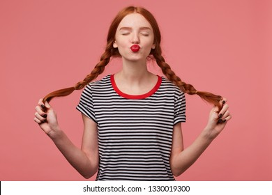 Sweet red-haired girl with red lips sends air kiss to a camera with closed eyes holding two braids in hands dressed in stripped t-shirt, flirting isolated on a pink background
