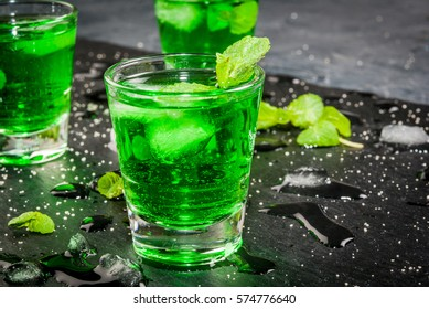 Sweet refreshing mint liqueur, with ice and mint leaves on the slate tray to feed on gray concrete stone table, close view