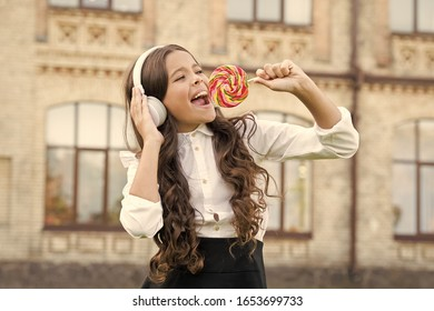 Sweet remix. Happy kid singing sweet candy mic. Happy childhood. Kid child headphones holding lollipop candy. Happy kid with candy outdoors having fun. Calories and energy. Schoolgirl deserve dessert.