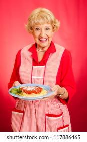 Sweet retro grandmother holding a plate of fresh, hot Italian Spaghetti with marinara sauce.  Red background.