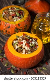 sweet rice with dried fruit and nuts in a pumpkin on wooden table, vertical, closeup