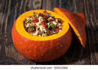sweet rice with dried fruit in a pumpkin on wooden table, closeup