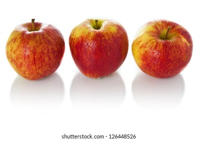 Sweet ripe red apples photographed on glass surface with reflection isolated on white background