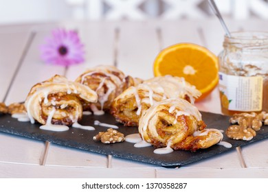 Sweet rolls with orange jam and walnuts. Background: half orange, a jar with jam and a flower.