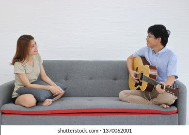 Sweet romantic young Asian couple playing acoustic guitar together in living room. Love and romance people concept.