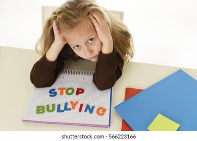 sweet sad and depressed young schoolgirl with stop bullying text on notebook  looking helpless and scared as victim of bullying at school in education problem concept isolated white background