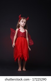 40232cf07 Sweet sad little girl standing alone on black background in red Halloween  costume.